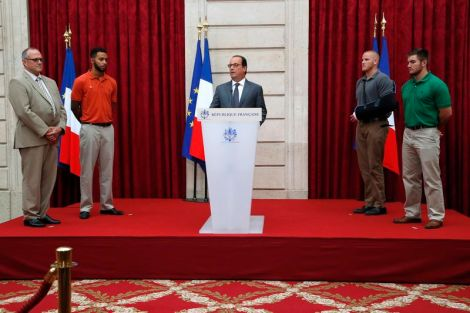 French President Francois Hollande delivers a speech as British businessman Chris Norman, U.S. student Anthony Sadler, U.S. Airman First Class Spencer Stone and U.S. National Guardsman Alek Skarlatos listen to during a ceremony at the Elysee Palace in Paris, France, August 24, 2015. (REUTERS/Michel Euler/Pool)